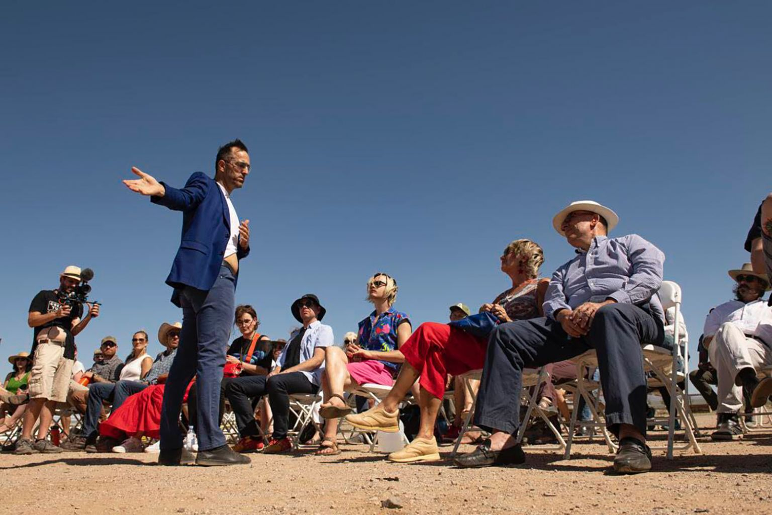 man performs for an audience in the desert