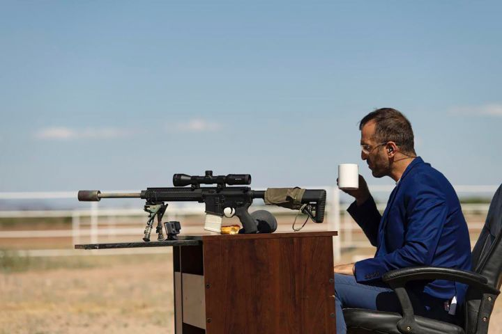 man with rifle drinks coffee at a desk in the desert