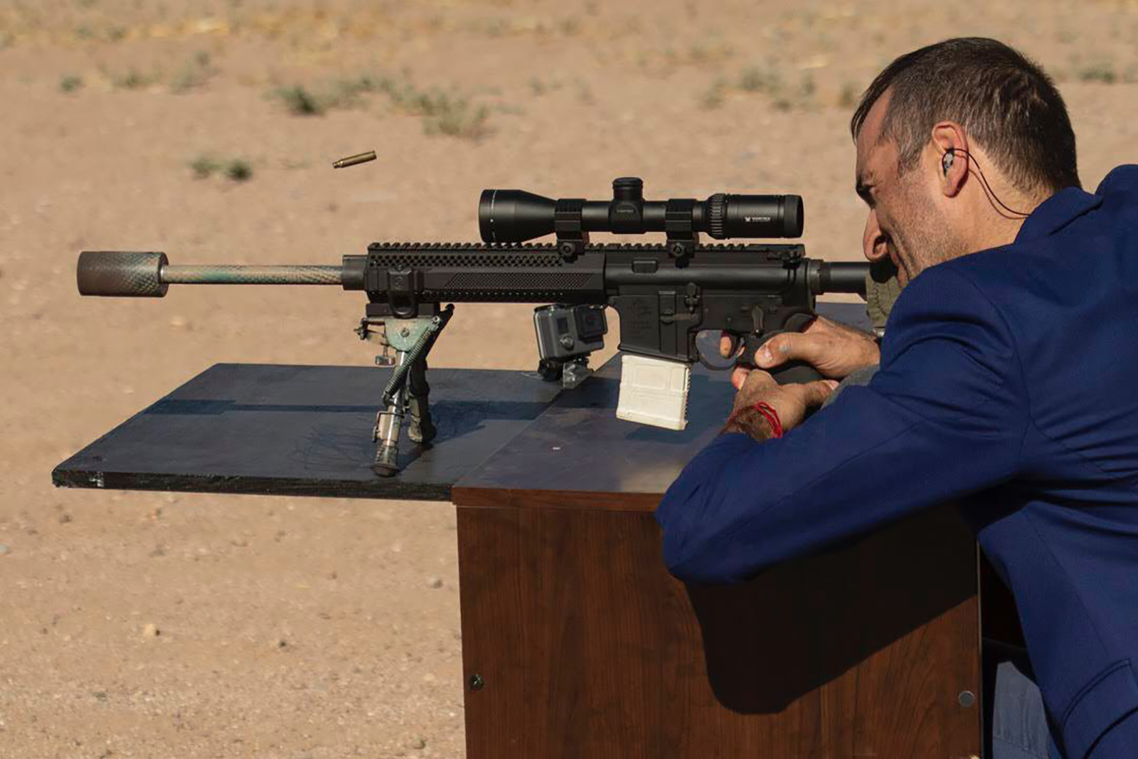 man fires a rifle from a desk in the desert